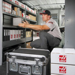 Haas technician pulling boxed item from a shelf in a service van